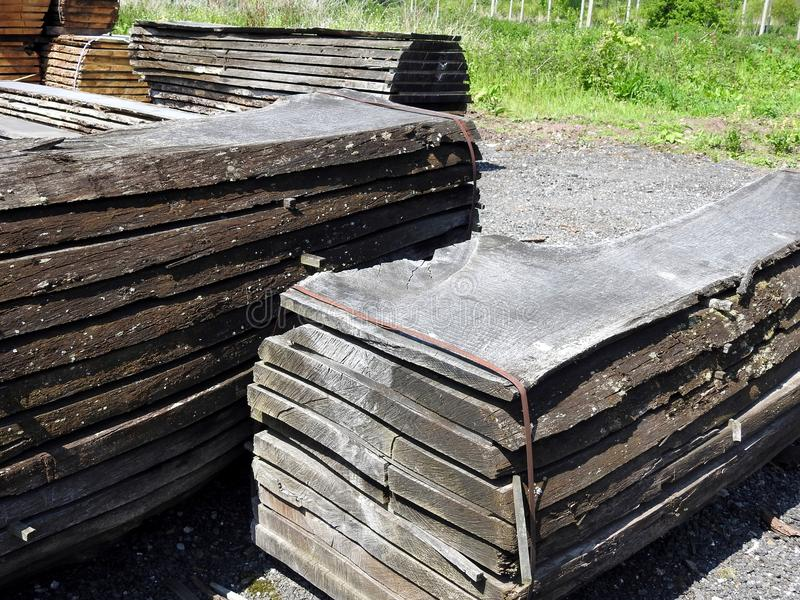 Piles of timber. Piles of rough cut timber, mainly oak planks strapped into bundles ready to be uplifted for joinery, house building and construction, grass stock photo