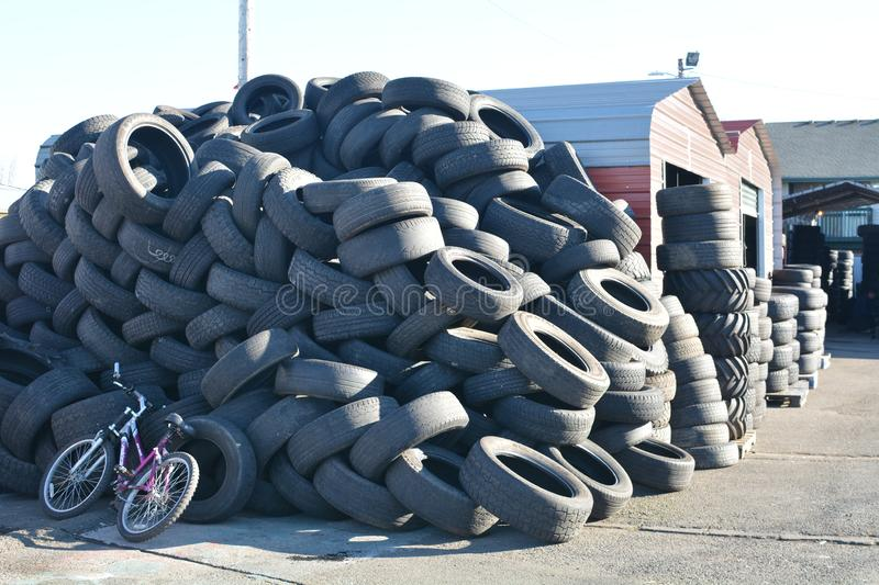 Piles of tires with bike in Salem, Oregon. This is a pile of black tires on a lot with bicycle in Salem, Oregon royalty free stock image