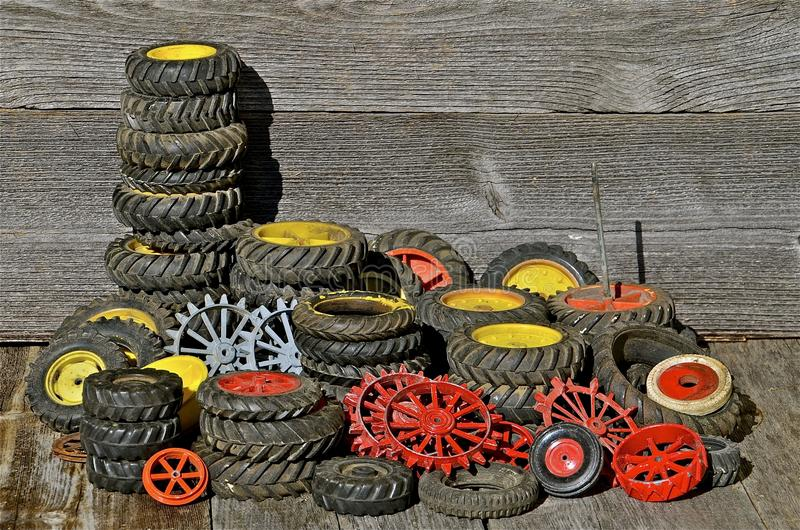 Piles of Toy Tractor Tires and Rims. A collection of old toy tractor tires and rims are displayed with a background of weathered wood stock photos