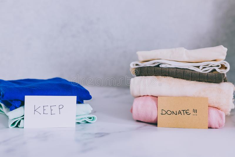 Piles of tshirts and clothes being sorted into Keep Discard and Donate categories. Decluttering and tidying up concept: piles of tshirts and clothes being sorted royalty free stock image