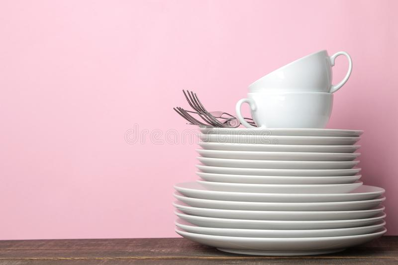 Piles of white ceramic tableware, plates, saucers, cups on a pink background. kitchenware stock images