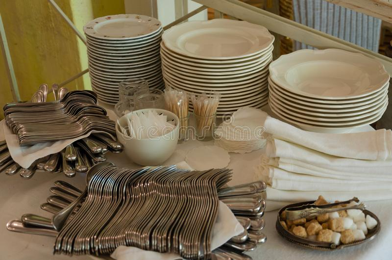 Piles of white clean plates, table knives, forks, spoons, napkins. Preparing for guest service in the restaurant. Piles of white clean plates, table knives stock photo