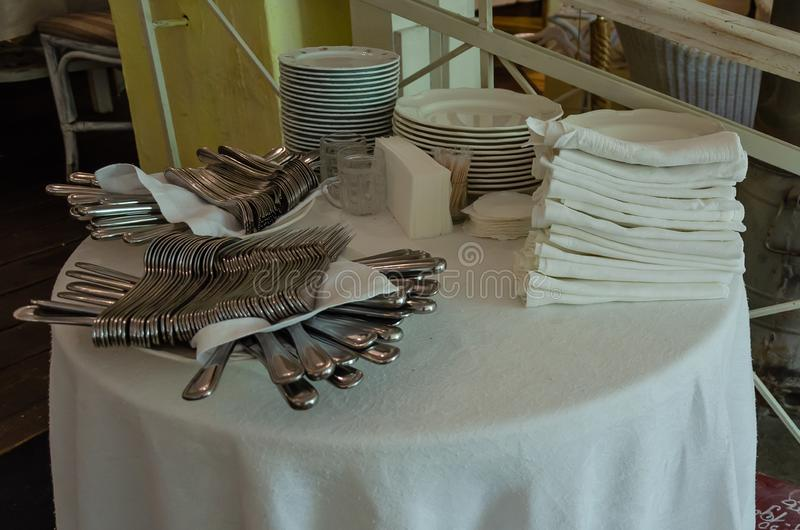 Piles of white clean plates, table knives, forks, spoons, napkins. Preparing for guest service in the restaurant. Piles of white clean plates, table knives stock image