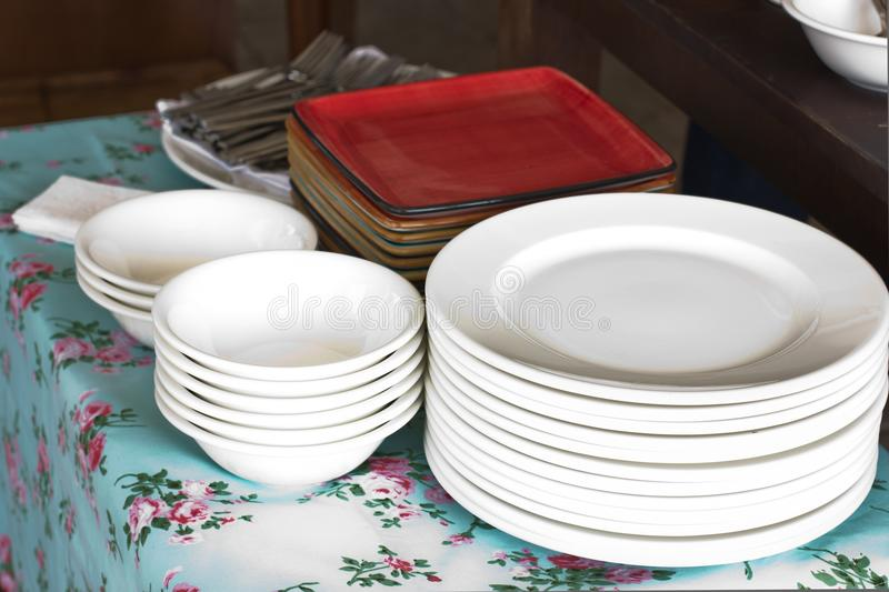 Piles of white round porcelain plates and red square plates royalty free stock images
