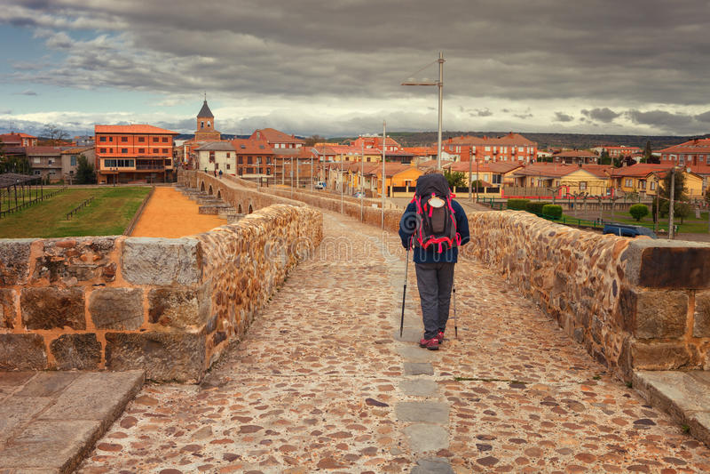 Pilger, welche die mittelalterliche Brücke über dem Fluss Orbigo, genannt Paso Honroso, Weise von St James, Spanien kreuzen stockbilder