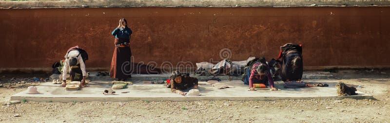Pilgerfrau beten außerhalb eines tibetanischen buddhistischen Tempels stockfotos