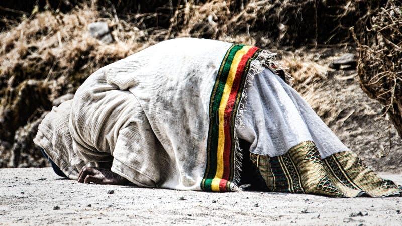 Pilgrim man in traditional white clothes praying royalty free stock photo