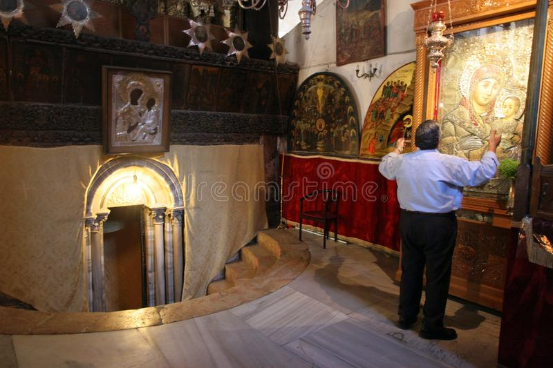 A pilgrim prays in front of the pictures of the Virgin with the Child Jesus, near the entrance to the cave of Jesus` birth, Bethle stock images