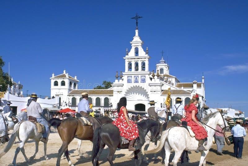 Pilgrims arriving at Hermitage in El Rocio, Spain. Spain, province of Huelva, Andalusia region: pilgrims arrive on horseback at the sanctuary church of the stock photo