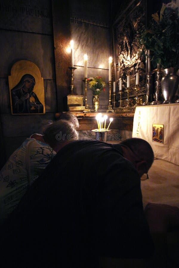 Pilgrims ber på gravvalvet av Jesus i Jerusalem royaltyfri bild