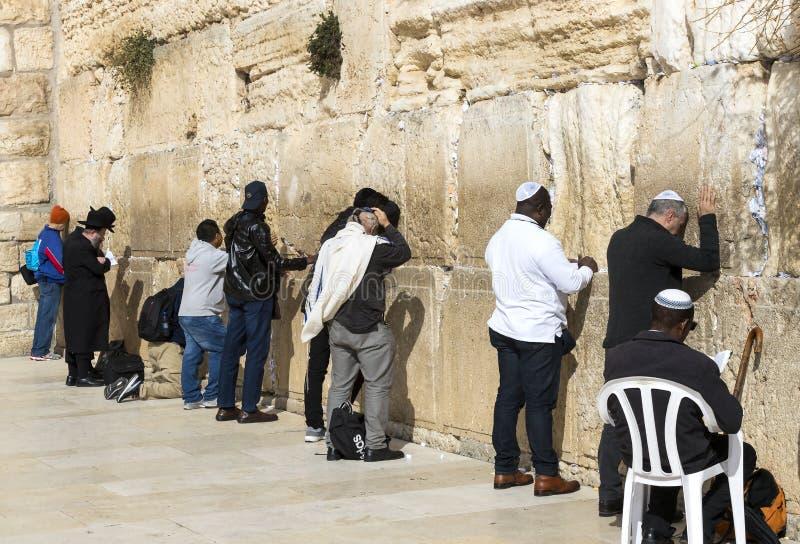 Pilgrims ber på väggen av gråta av det heliga stället av det judiska folket och mitten av dyrkan av kristen runt om royaltyfri bild