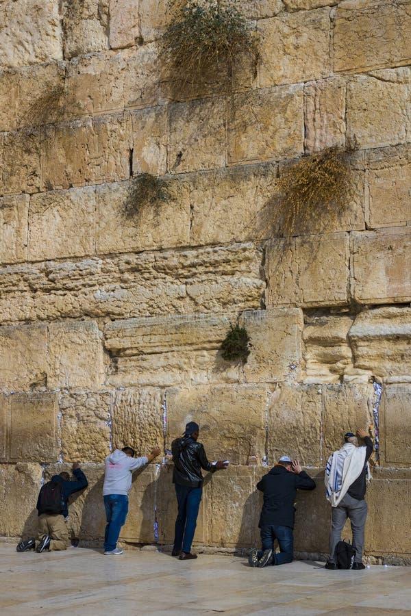 Pilgrims ber på väggen av gråta av det heliga stället av det judiska folket och mitten av dyrkan av kristen runt om arkivbild