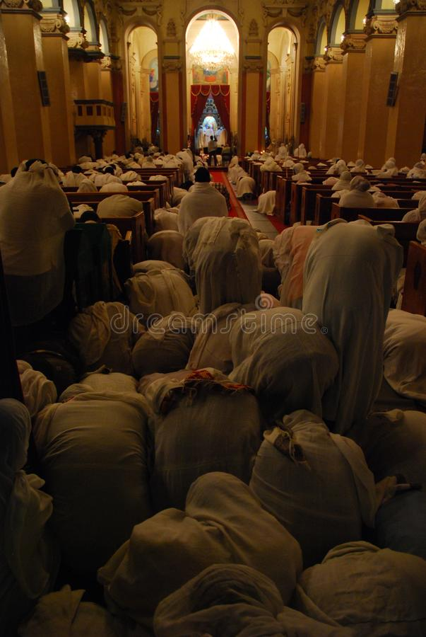 Pilgrims bowing during mass service. Pilgrims following mass service during Ethiopian Christmas stock images