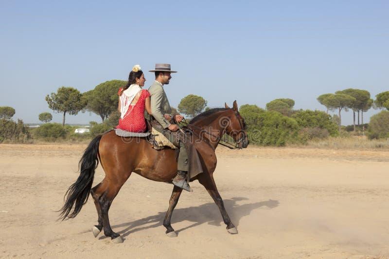 Pilgrims on horseback in El Rocio, Spain. El Rocio, Spain - June 1, 2017: Couple on horseback in traditional spanish dress on the road to El Rocio during the royalty free stock photography