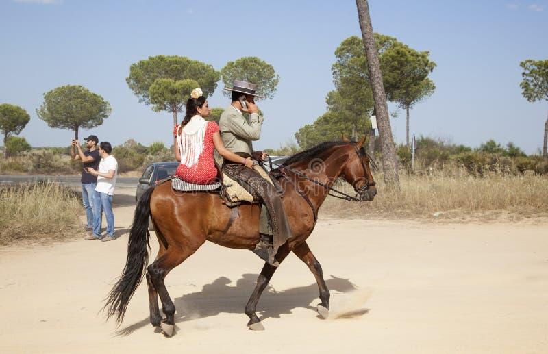Pilgrims on horseback in El Rocio, Spain. El Rocio, Spain - June 1, 2017: Couple on horseback in traditional spanish dress on the road to El Rocio during the stock image