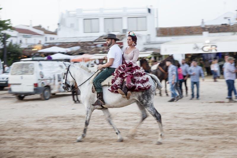 Pilgrims on horseback in El Rocio, Spain. El Rocio, Spain - June 1, 2017: Couple on horseback in traditional spanish dress in El Rocio during the Romeria 2017 royalty free stock photography
