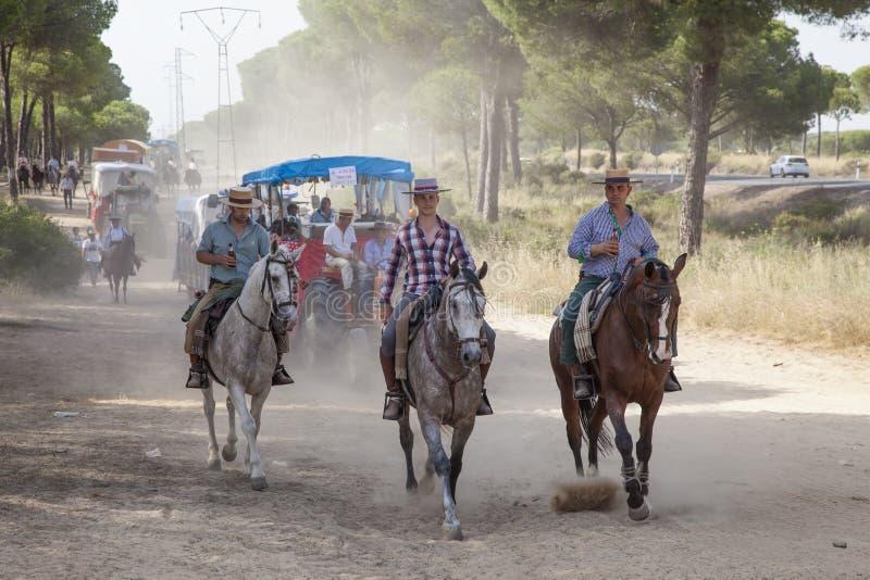 Pilgrims on horseback in El Rocio, Spain. El Rocio, Spain - June 1, 2017: Pilgrims on horseback in traditional spanish dress on the road to El Rocio during the stock image