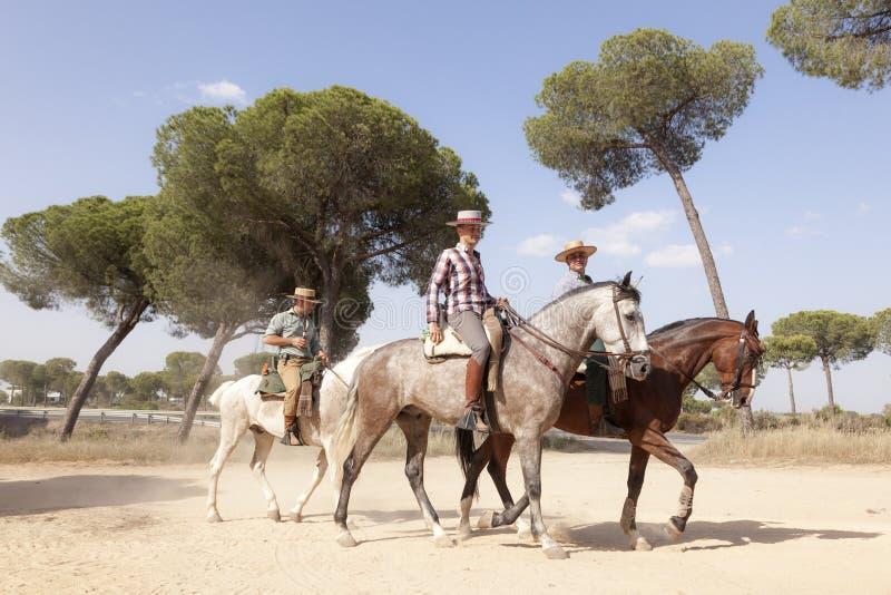 Pilgrims on horseback in El Rocio, Spain. El Rocio, Spain - June 1, 2017: Pilgrims on horseback in traditional spanish dress on the road to El Rocio during the royalty free stock photography