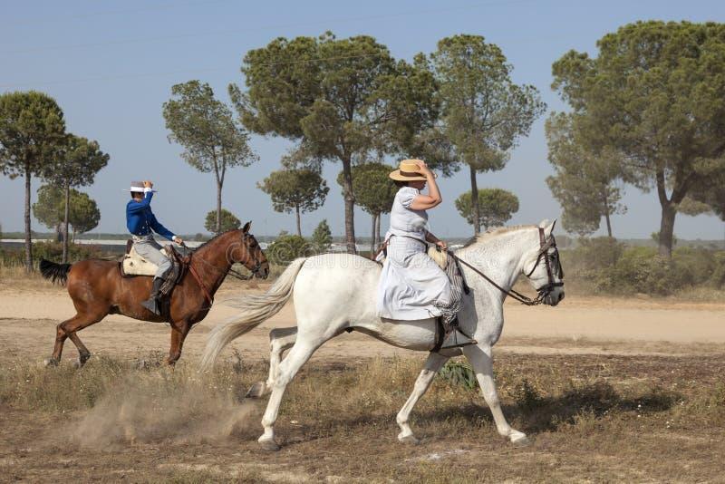 Pilgrims on horseback in El Rocio, Spain. El Rocio, Spain - June 1, 2017: Pilgrims on horseback in traditional spanish dress on the road to El Rocio during the stock photos