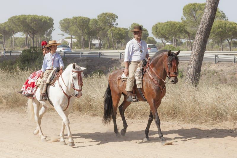 Pilgrims on horseback in El Rocio, Spain. El Rocio, Spain - June 1, 2017: Pilgrims on horseback in traditional spanish dress on the road to El Rocio during the royalty free stock photos