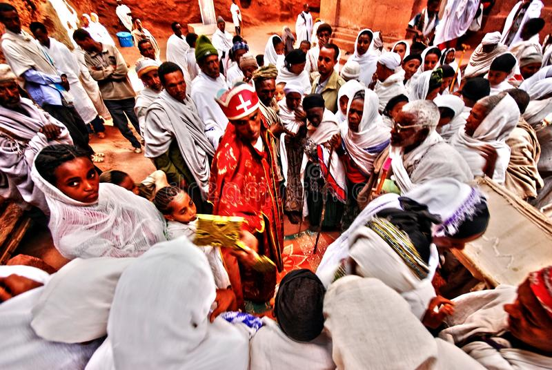 Lalibela, Wollo, Ethiopia, circa november 2008: Pilgrims kissing cross after atending the service outside of rock hewn church royalty free stock photography