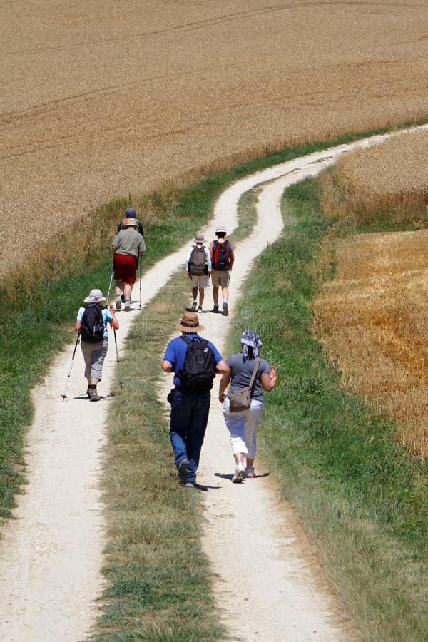 Pilgrims. LA ROMIEU, FRANCE, June 24, 2015 : A group of pilgrims walks on the path of the Chemins de Compostelle. Pilgrimage to Santiago de Compostela has been royalty free stock photo