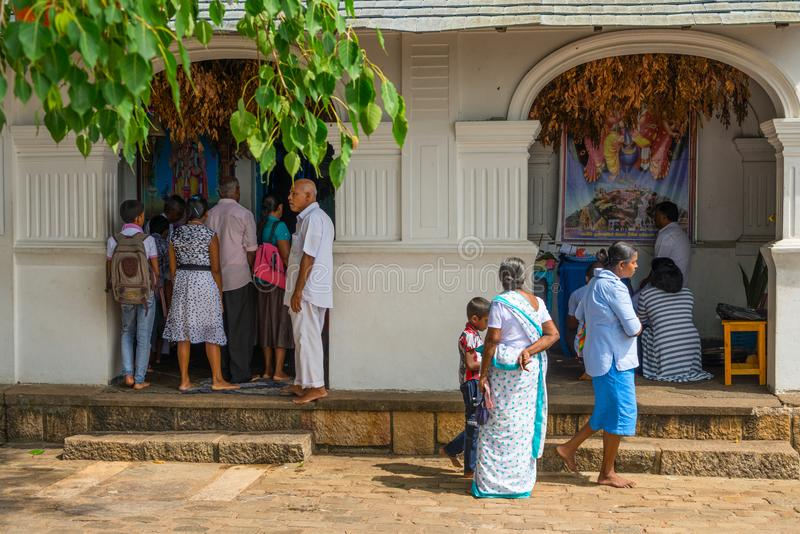 Pilgrims near small Vishnu shrine in Golden cave temple complex. DAMBULLA, SRI LANKA - NOV 2016: Pilgrims near small Vishnu shrine in Golden cave temple complex royalty free stock photos