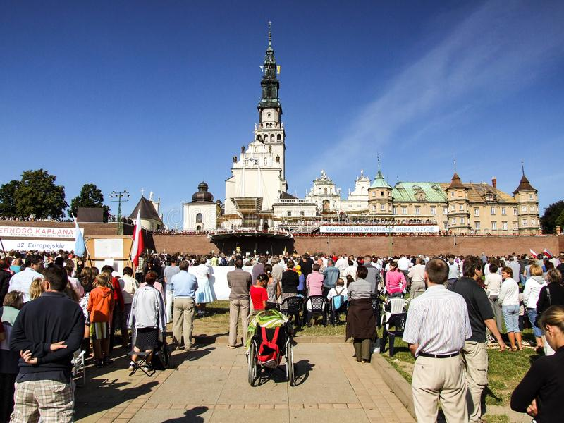 People are praying at Jasna Gora Monastery in Czestochowa in Poland. Pilgrims participate in devotion on square at Jasna Gora. Many people seen from behind royalty free stock photography