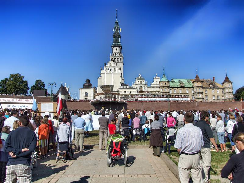 People are praying at Jasna Gora Monastery in Czestochowa in Poland. Pilgrims participate in devotion on square at Jasna Gora. Many people seen from behind royalty free stock images