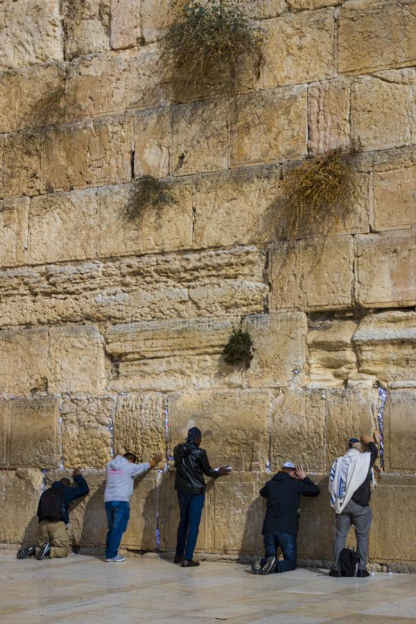 Pilgrims pray at the wall of the weeping of the holy place of the Jewish people and the center of worship of Christians around the stock photography