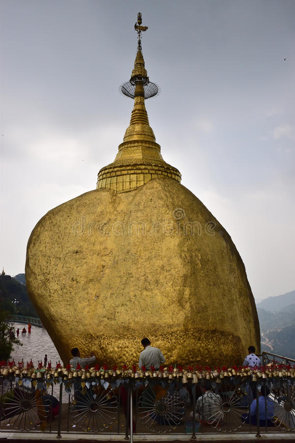 Pilgrims praying and pasting gold foils together onto golden rock at the Kyaiktiyo Pagoda, Myanmar with row of small bells stock photo