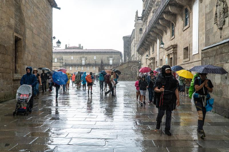 Pilgrims and tourists walking on a rainy day street of old town of Santiago de stock images