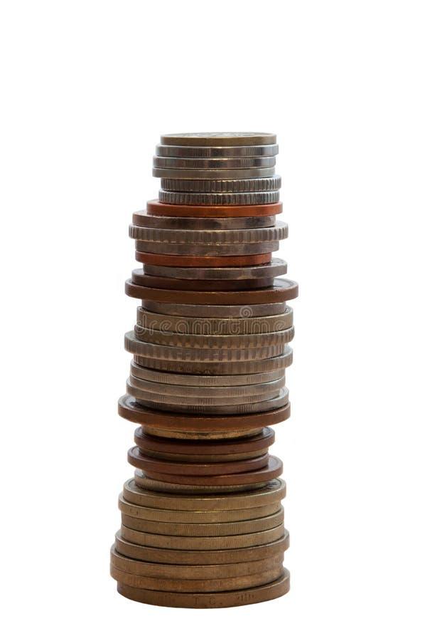 Pilha alta de moedas em um fundo branco isolado verticalmente imagens de stock royalty free