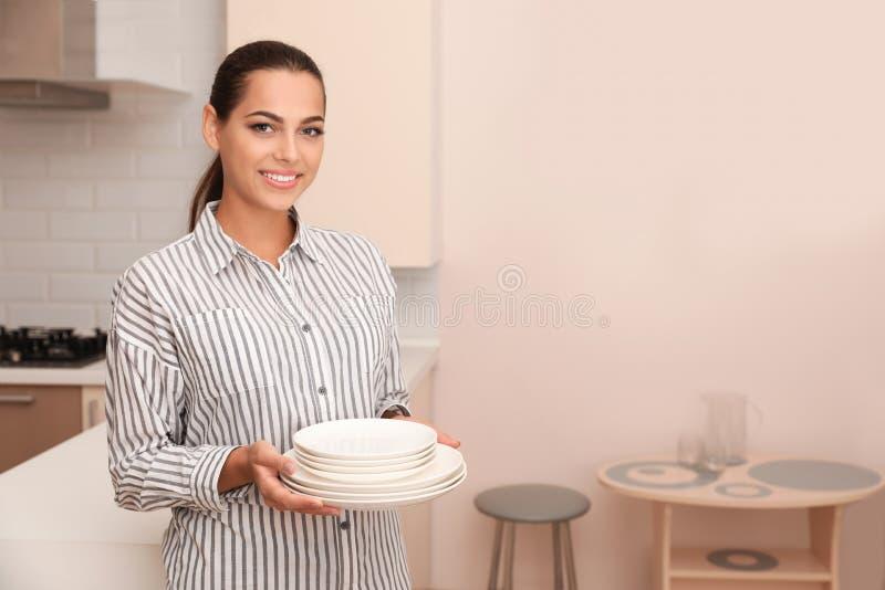 Pilha bonita da terra arrendada da jovem mulher de pratos limpos imagens de stock
