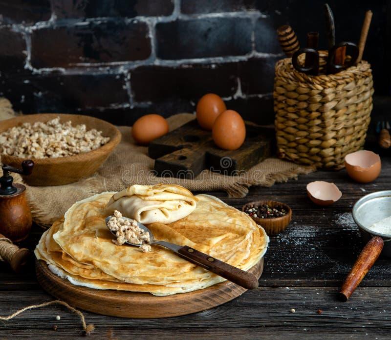 Pilha caseiro de crepes no suporte de madeira da placa na tabela rústica com a placa da carne fritada à terra imagens de stock royalty free