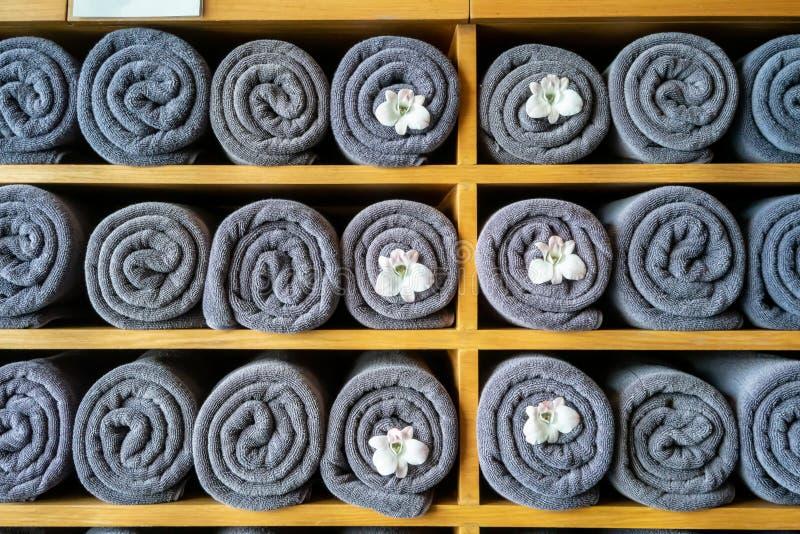 Pilha cinzenta rolada delicada de toalhas com a orquídea branca para a decoração na prateleira no banheiro fotografia de stock