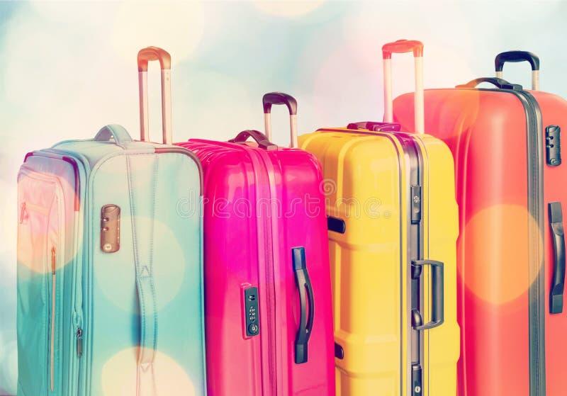 Pilha colorida das malas de viagem no fundo da cidade fotografia de stock