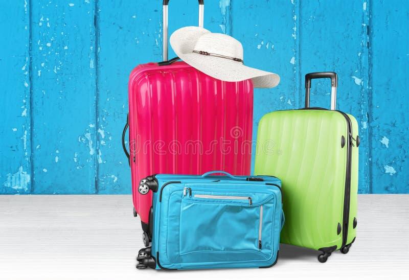 Pilha colorida das malas de viagem no fundo de madeira imagem de stock