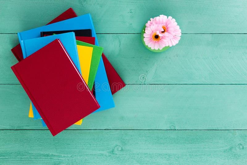 Pilha colorida dos livros empilhados em uma tabela verde fotografia de stock royalty free