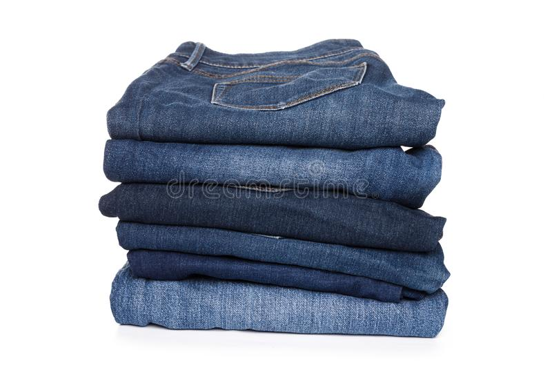 Pilha da calças das calças de brim no fundo branco imagem de stock