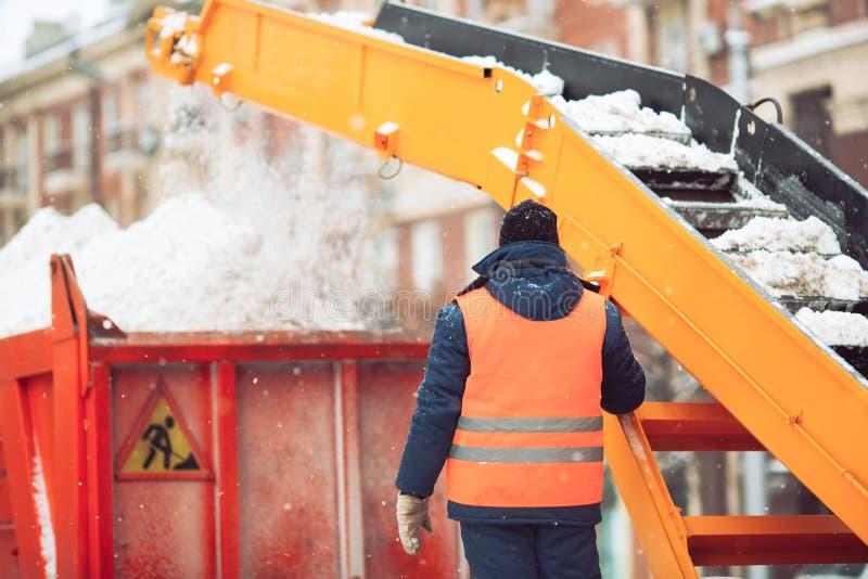 Pilha da carga da m?quina da neve-remo??o do trator da limpeza da neve da neve em um caminh?o basculante Cidade de limpeza da rua fotografia de stock