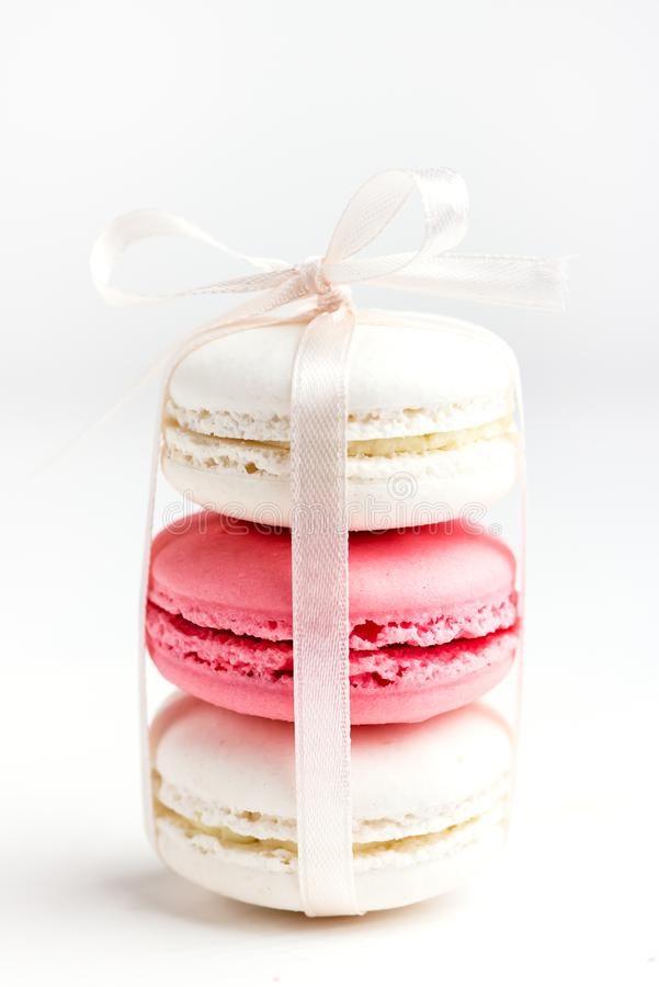 Pilha da cor pastel e de Macarons saboroso no fim branco e cor-de-rosa branco do fundo de Macaron do vertical acima fotos de stock