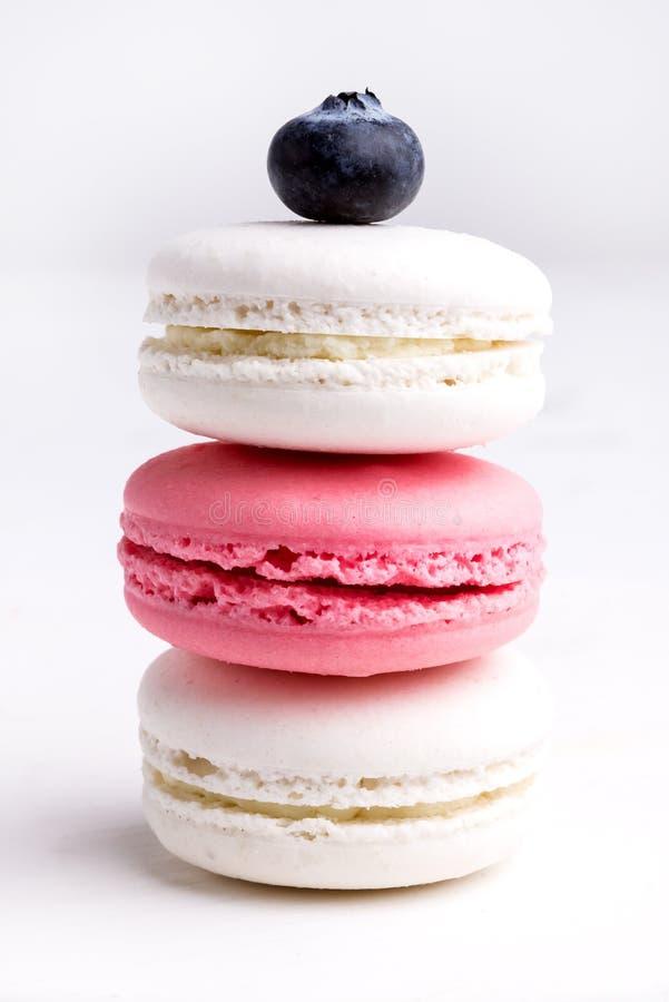 Pilha da cor pastel e de Macarons saboroso no fim branco e cor-de-rosa branco do fundo de Macaron do vertical acima imagens de stock royalty free
