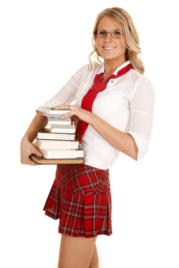 Pilha da menina da escola de sorriso dos livros fotografia de stock royalty free