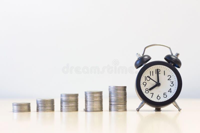 Pilha da moeda do despertador e do dinheiro no tanle da mesa desenvolvimento sustentável da finança fotografia de stock