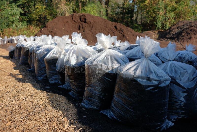 Pilha da palha de canteiro com os sacos da palha de canteiro fotografia de stock