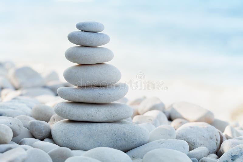 Pilha da pedra branca dos seixos contra o fundo do mar para o tema dos termas, do equilíbrio, da meditação e do zen imagens de stock