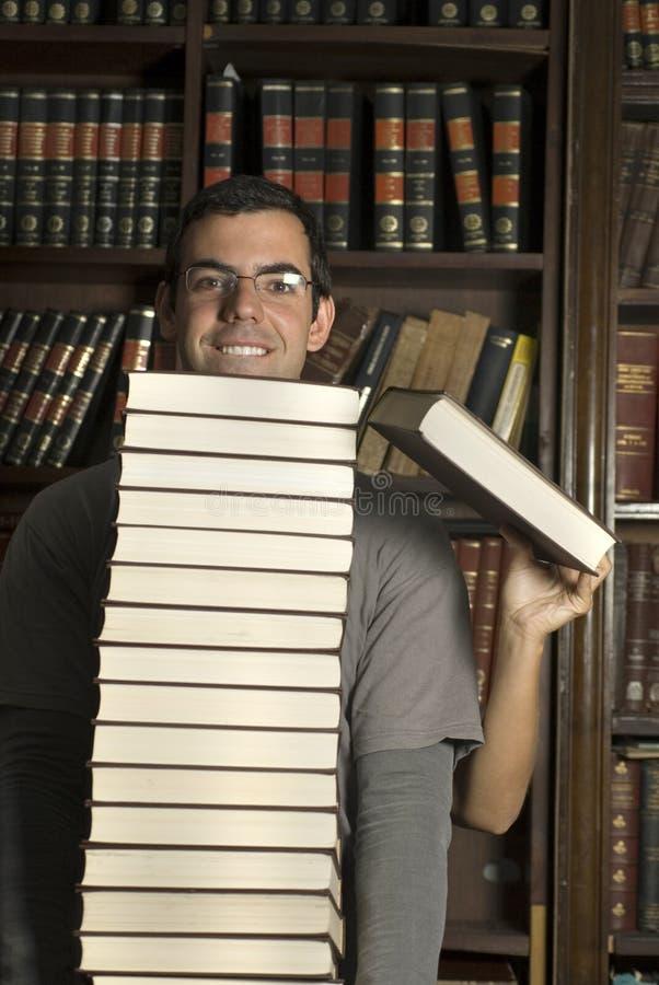 Pilha da preensão dos pares de livros na biblioteca - vertical foto de stock