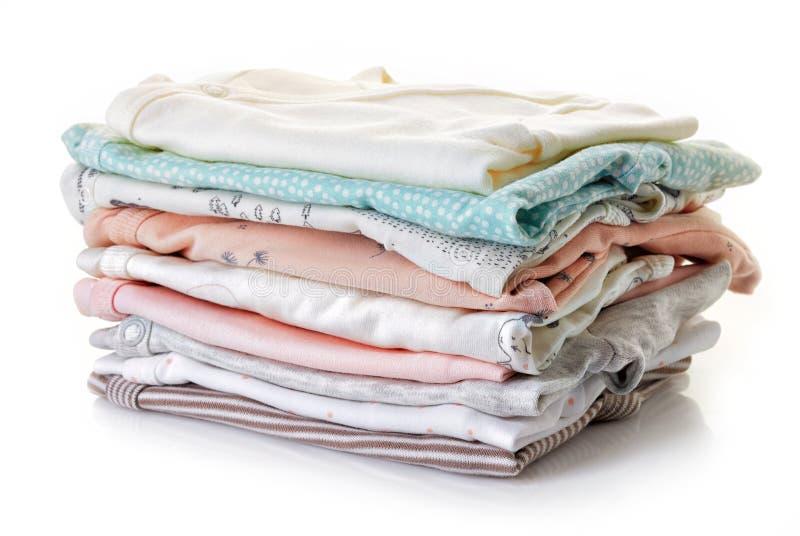 Pilha da roupa do bebê isolada no branco imagem de stock