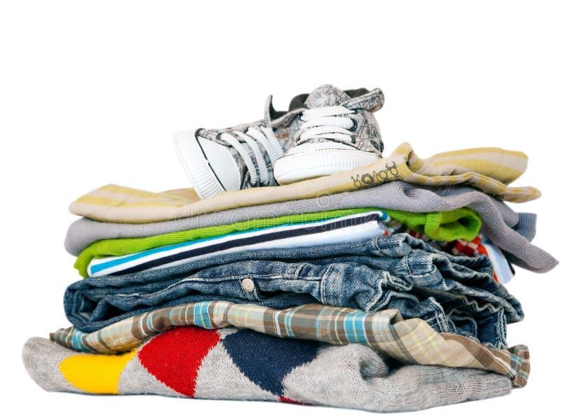Pilha da roupa e das sapatilhas isoladas no branco imagens de stock